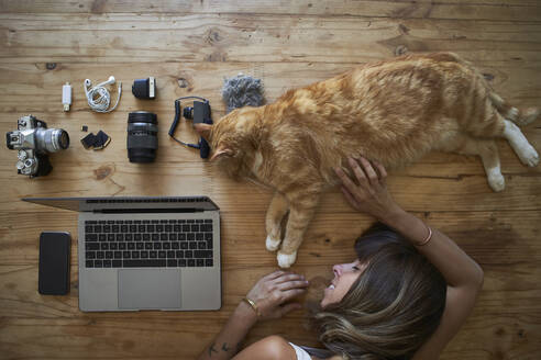 Exhausted woman sleeping on table with ginger cat, laptop and photografic equipment - VEGF01226