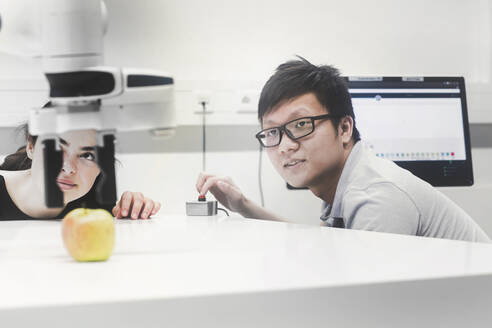 Sudents studying robotic at an university institute, making experiments with an apple - SGF02516