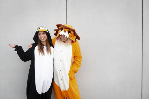 Two women in penguin and lion costume in front of concrete wall - HMEF00706