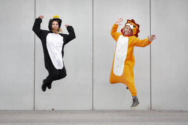Two women in penguin and lion costume jumping in front of concrete wall - HMEF00709