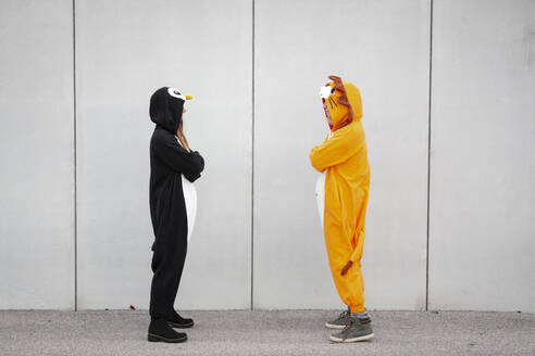 Two women in penguin and lion costume standing opposite in front of concrete wall - HMEF00712