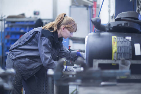 Female car mechanic working in repair garage - SGF02527