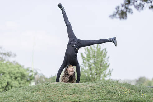 Girl doing a handstand on a meadow - STBF00513