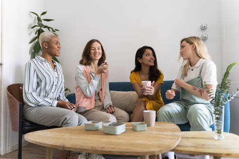 Four women sitting on couch talking - AFVF04470