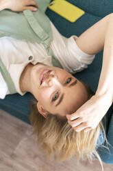 Portrait of smiling young woman lying on couch - AFVF04485