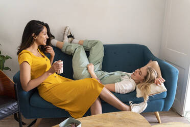 Two happy young women relaxing on couch - AFVF04488