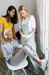 Three women with headphones and cell phone at the window - AFVF04503