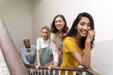 Portrait of four happy women in staircase - AFVF04509