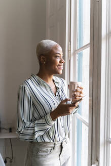 Happy woman with cell phone and coffee cup looking out of window - AFVF04515