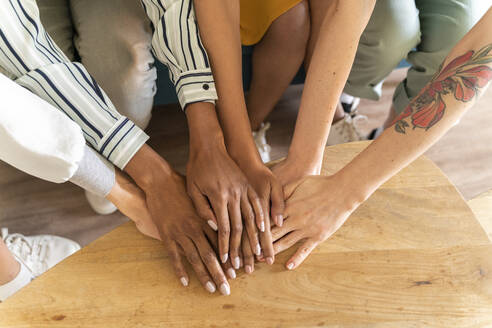 Close-up of four women stacking hands - AFVF04524