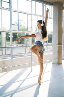 Ballerina with headphone dancing in gym - MPPF00402
