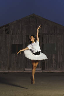 Ballerina dancing in front of a wooden hut in the evening - MPPF00417
