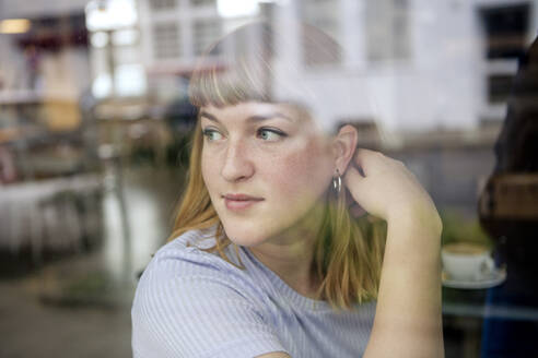 Portrait of young woman in a cafe looking out of window - FLLF00364