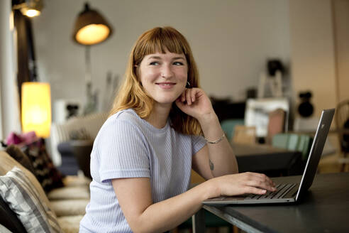 Portrait of strawberry blonde young woman with nose piercing using laptop in a coffee shop - FLLF00370