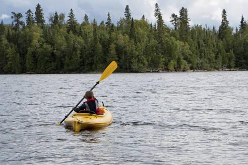 Rear view of boy canoeing in lake - CAVF70846