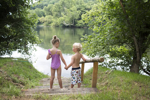 High angle view of siblings holding hands while standing on steps against lake - CAVF70861
