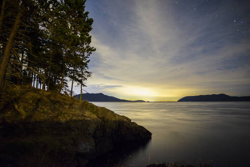 Idyllic view of lake by mountains against star field - CAVF70936