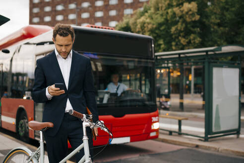 Businessman using smart phone while standing with bicycle against bus on street in city - MASF15514