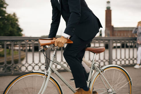 Low section of businessman riding bicycle on bridge in city - MASF15517