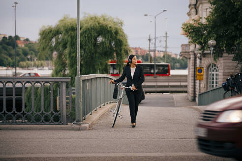 Businesswoman looking away while walking with bicycle on bridge in city - MASF15520