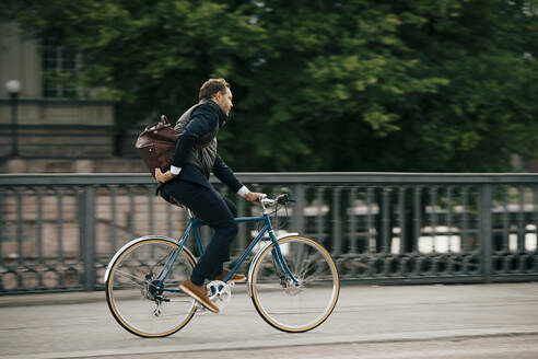 Side view of businessman with bag riding bicycle on bridge - MASF15523