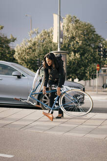 Businesswoman holding bicycle while crossing street in city - MASF15541