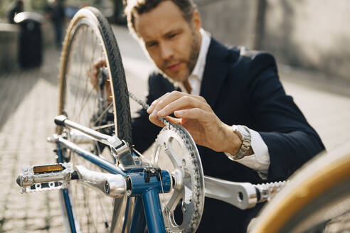 Businessman repairing bicycle chain in city on sunny day - MASF15550