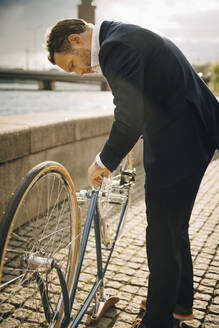 Side view of businessman repairing bicycle on footpath in city during sunny day - MASF15553