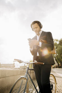 Businessman using mobile phone while standing by bicycle against sky during sunny day - MASF15562