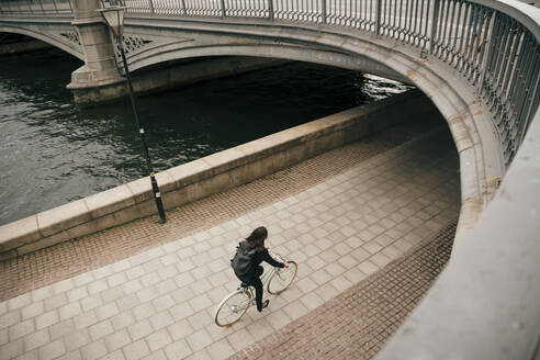 High angle view of businesswoman riding bicycle on footpath by canal in city - MASF15571