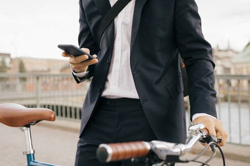 Midsection of businessman using smart phone while standing with bicycle on bridge in city - MASF15586