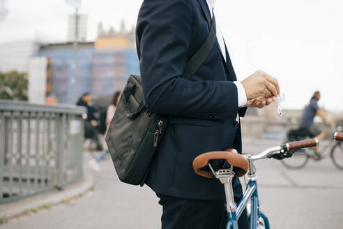 Midsection of businessman holding in-ear headphones while standing with bicycle on bridge in city - MASF15589