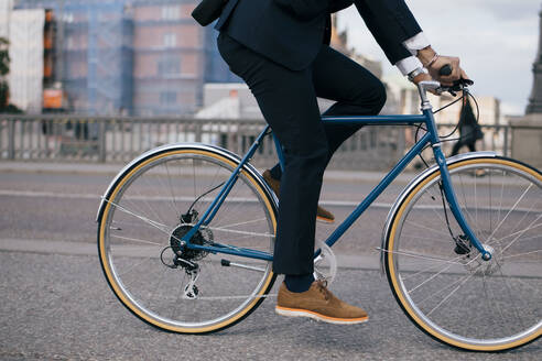 Low section of businessman riding bicycle on street in city - MASF15598