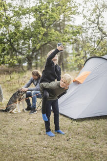 Boy piggybacking sister with smart phone while man playing with dog at tent camping - MASF15634