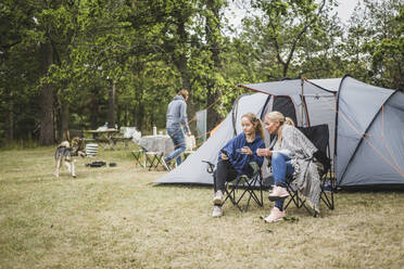 Mother and daughter having coffee while looking at mobile phone in campsite - MASF15637