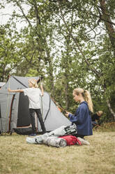Teenage girl using phone while family pitching tent at camping site - MASF15652