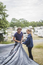 Teenage girl assisting father in pitching tent at campsite - MASF15661