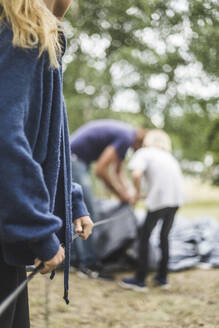 Midsection of teenage girl assisting family in pitching tent at campsite - MASF15667