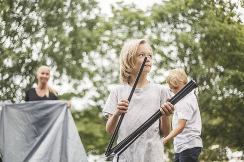 Girl with poles assisting family in pitching tent at campsite - MASF15670