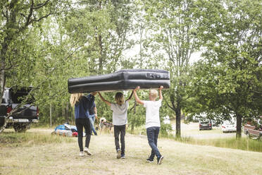 Children carrying inflatable mattress while walking towards car at camping site - MASF15673