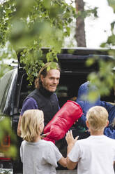 Smiling father giving luggage to children while unloading from car - MASF15679