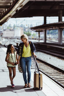 Full length of mother and daughter with luggage walking at railroad station - MASF15802