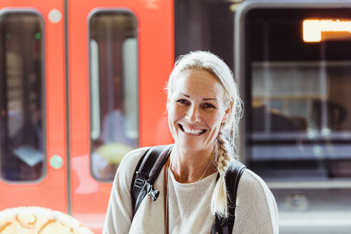 Portrait of smiling mature woman with backpack standing at train station - MASF15835