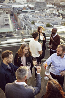 High angle view of coworkers toasting wineglasses while partying at building terrace - MASF15913