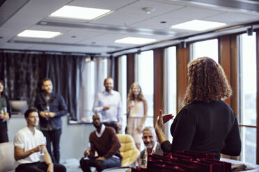 Businesswoman giving speech to coworkers during office party after work - MASF15925