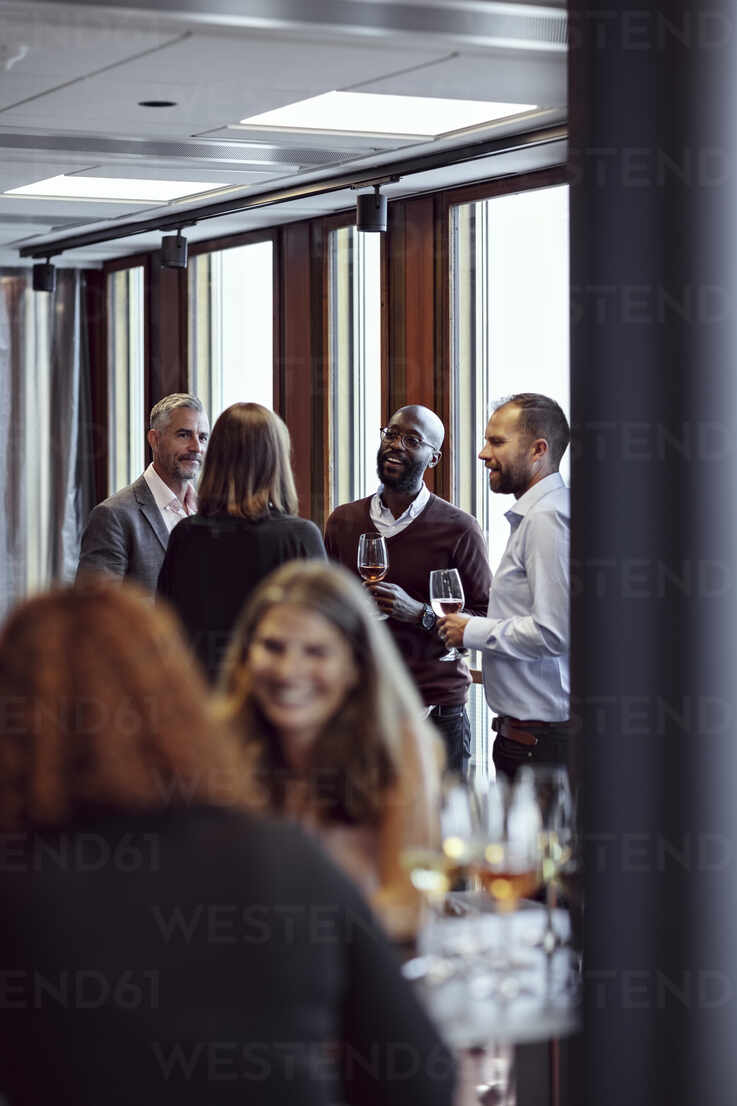 Professionals discussing over drinks at conference in office - MASF15928 - Maskot/Westend61