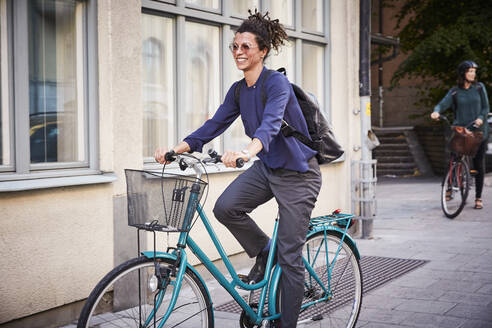 Smiling young female architect riding bicycle on street in city - MASF15934