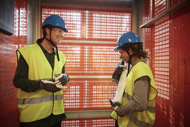 Smiling female engineers discussing while standing in freight elevator at construction site - MASF15973