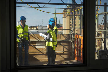 Male and female engineers seen through window at construction site - MASF15976