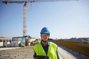 Confident female engineer in reflective clothing with digital tablet at construction site against clear sky - MASF15982